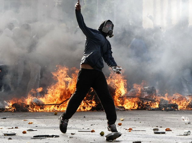 A protester throws stones at policemen during clashes in central Athens